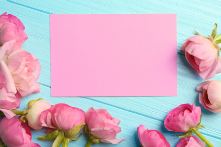 Beautiful ranunculus flowers and card on blue wooden background Archivio Fotografico