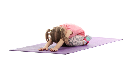 Cute girl doing gymnastic exercises on mat, isolated on white Foto de archivo
