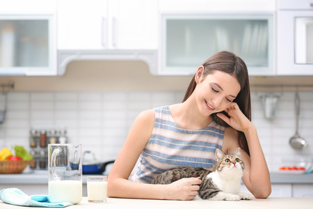 Morning of beautiful young woman and cat in kitchen Stock Photo