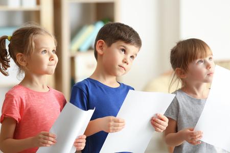 Cute kids singing in music class Фото со стока