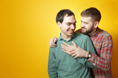 Happy gay couple posing on yellow background