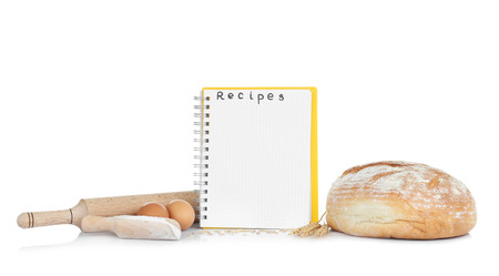 Open recipe book and bread on white background