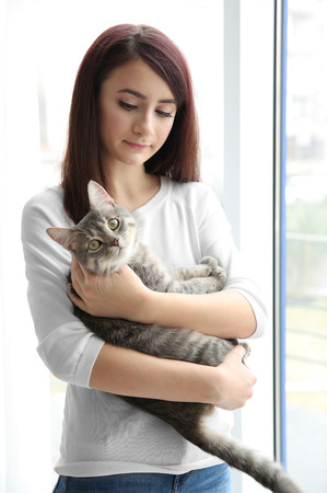 Beautiful young woman with cute cat near window at home Фото со стока
