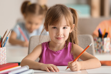 Cute girl drawing in classroom