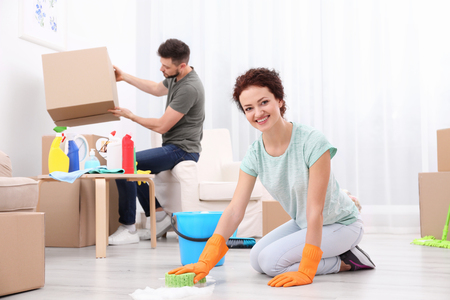 Happy young couple cleaning home together