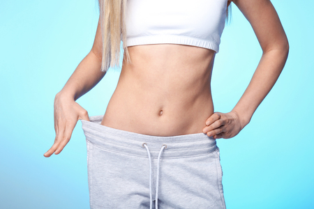 Diet concept. Young beautiful woman in big pants on light background Stock fotó