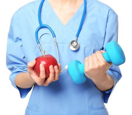 Diet concept. Female nutritionist with apple and dumbbell on white background Stock Photo