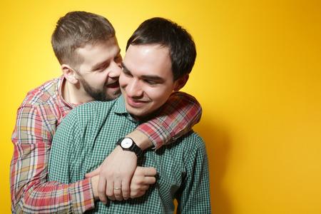 Happy gay couple posing on yellow background