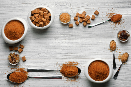 Composition with brown sugar on wooden background