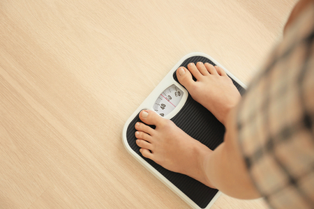 Diet concept. Female bare feet standing on scales Standard-Bild