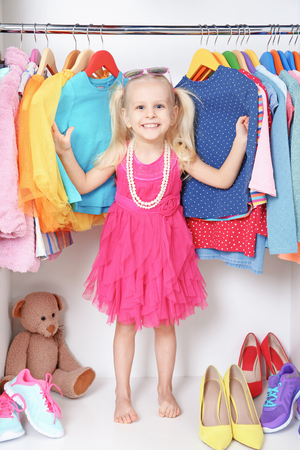 Cute small girl in wardrobe with clothes Imagens