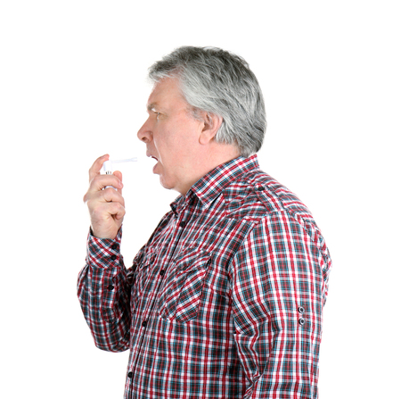 Sick senior man using throat spray on white background Foto de archivo