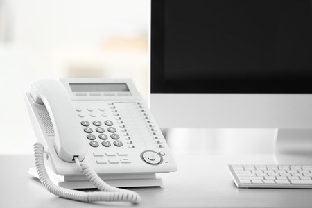 Telephone and computer on table in office