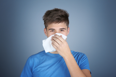 Young man blowing nose on tissue against color background Фото со стока