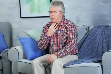 Sick senior man having pain in throat at home Stock Photo