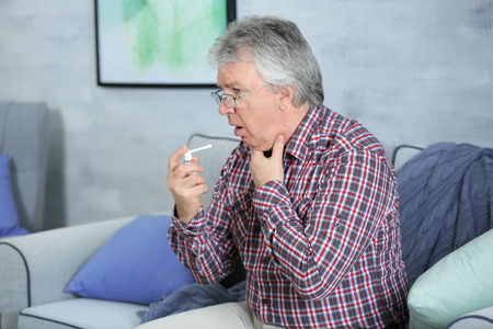 Sick senior man using throat spray at home