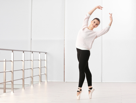 Ballet art concept. Young beautiful ballerina training in dance hall