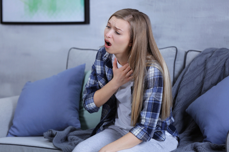 Sick young woman coughing at home
