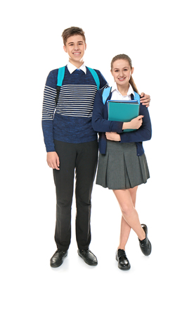 Cheerfully smiling boy and girl in elegant school uniform standing on light background