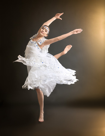 Young beautiful ballerina on dark background