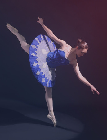 Young beautiful ballerina on dark background