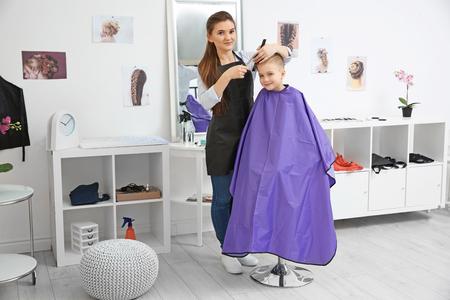 Mignon petit garçon dans un salon de coiffure