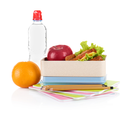 Appetizing sandwich, red apple in lunch box and stationery on white background
