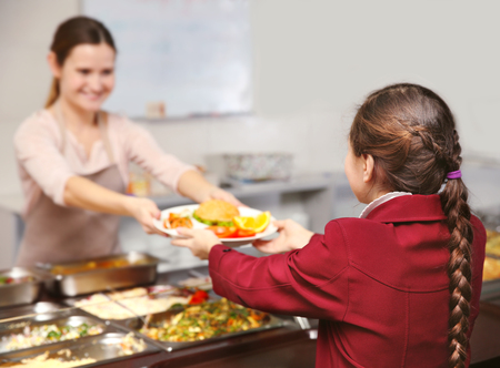Pleasant woman giving lunch to school girl in cafeteria Banque d'images