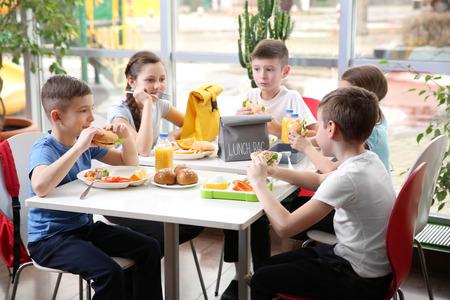 Kinder sitzen beim Mittagessen am Kantinentisch