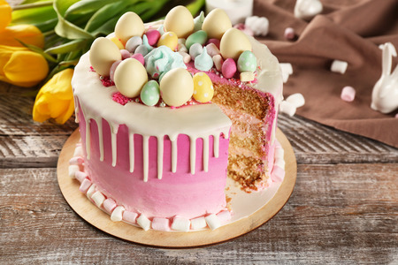 Sliced delicious Easter cake on wooden festive table