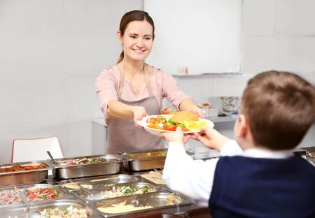 Angenehme Frau, die dem Schuljungen in der Cafeteria Mittagessen gibt