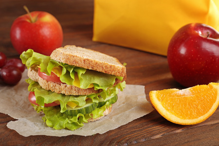 Delicious sandwich and fresh fruits on wooden background