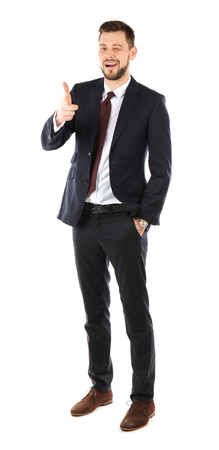 Handsome businessman in elegant suit winking and pointing on white background 스톡 콘텐츠