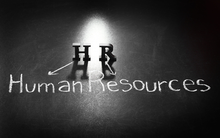 Letters HR and text HUMAN RESOURCES written with chalk on blackboard background 版權商用圖片