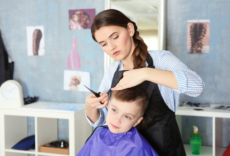 Cute little boy in hairdressing salon