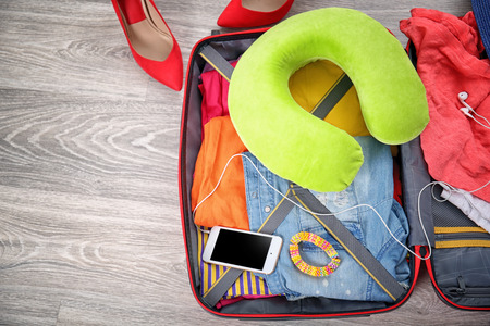 Suitcase with different things prepared for travel on floor