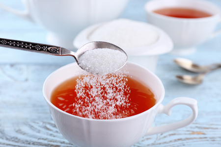 Adding sugar to cup of black tea on wooden table Stock fotó - 110709704