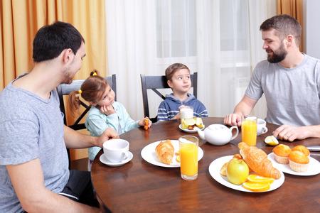 Pareja masculina con niños desayunando en la cocina