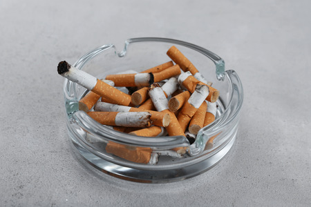 Cigarette butts in ashtray on light background Stock Photo
