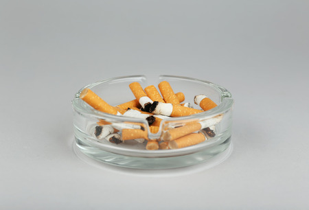 Cigarette butts in ashtray on light background Imagens