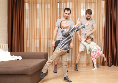 Male gay couple with children having fun at home