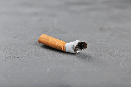 Cigarette butt on gray background Stock Photo