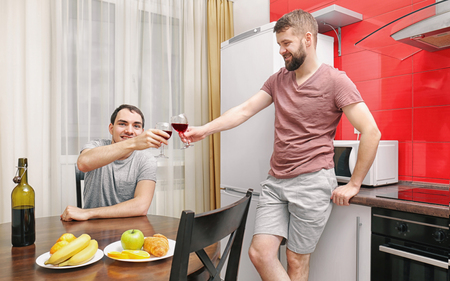 Gay couple drinking wine in kitchen