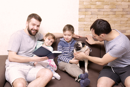 Male couple with children sitting on sofa at home