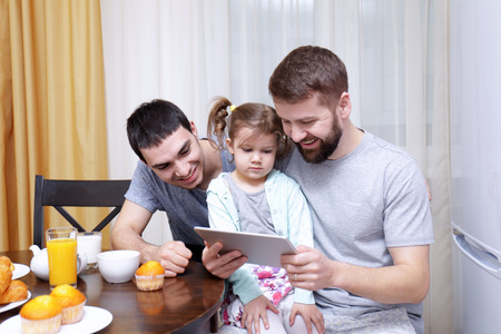 Male couple with daughter having breakfast in kitchen