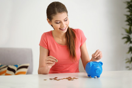 Beautiful young woman putting coins into piggy bank at home
