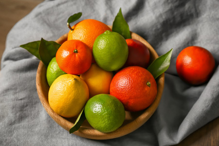 Composition of different citrus fruits in bowl on napkin, closeup