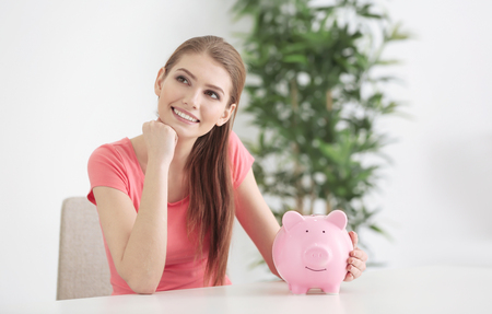 Beautiful young woman with piggy bank at home Reklamní fotografie