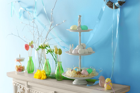 Beautiful composition of Easter symbols and treats on wooden mantelpiece