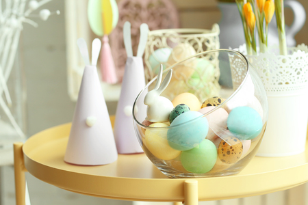 Glass vase with painted Easter eggs and handmade paper rabbits on table Reklamní fotografie